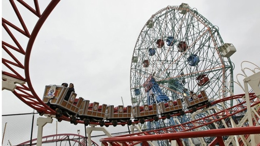 Visitors to Coney Island ride the Circus Coaster, foreground, and the Wonder Wheel, background, during opening day at Luna Park in Brooklyn, New York, Saturday, April 16, 2011. The opening of Luna Park and the Cyclone marked the beginning of the season in Coney Island.