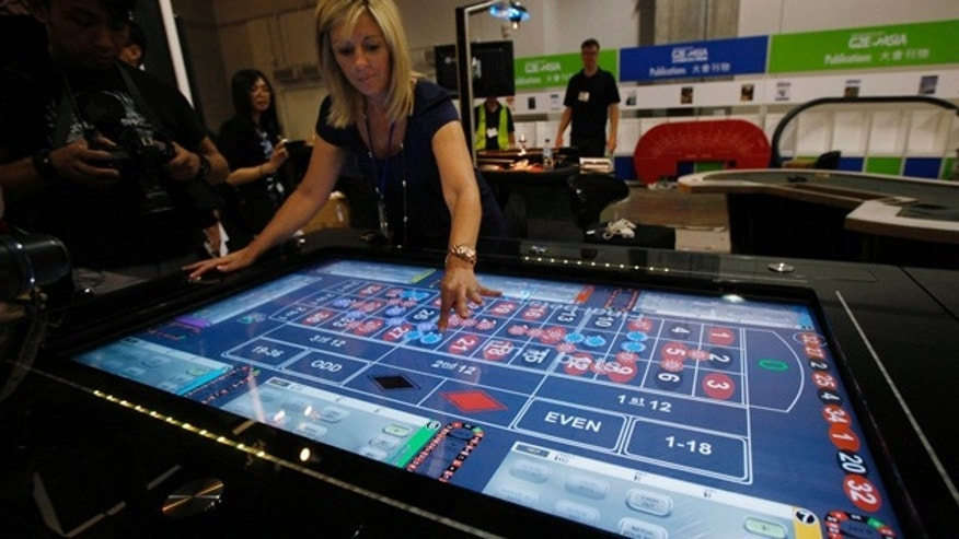 A staff member demonstrates a table gambling game at the Global Gaming Expo Asia in Macau Tuesday, June 7, 2011. Asia will be home to the world's two biggest casino markets as early as this year, with Singapore set to take the No. 2 spot from Las Vegas, Frank Fahrenkopf, president of the American Gaming Association said Tuesday. (AP Photo/Kin Cheung)