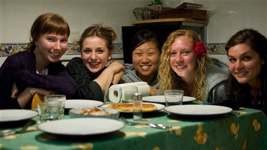 """This March 7, 2010 photo provided by Lauren Hook shows her, left, a new Spanish friend, Carmen Lleo Badal, and other U.S. students Grace Choi, Leah Kosmoski, and Laura Grace Janeskiss before eating a traditional Spanish tortilla omelet at Lleo Badal's family home in Castellon, Spain during the Magdalena Festival. After decades of laissez-faire and faith that just breathing the air in foreign lands broadens horizons, American colleges and international programs are pressing students harder to get out of their comfort zones. """"I noticed a lot of these kids, first time out of the country, all they wanted to do was party, said Hook, a University of Georgia senior who spent the spring of 2010 in Spain. The embarrassing sight of fellow Georgia students stumbling drunkenly around Valencia belting out Bulldog fight songs pushed her to explore more on her own. She also appreciated program activities setting up meetings between American students and locals. Meeting a Spanish boyfriend also helped. (AP Photo)"""