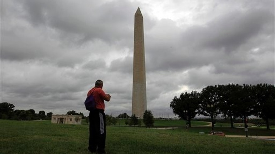 A tourist takes a picture of the recently damaged Washington Monument as clouds from Hurricane Irene moves up the Eastern Seaboard towards Washington, Saturday, Aug. 27, 2011.  The monument has been closed to the public it was damaged in the earthquake that shook the capital last Tuesday. (AP Photo/Luis M. Alvarez)