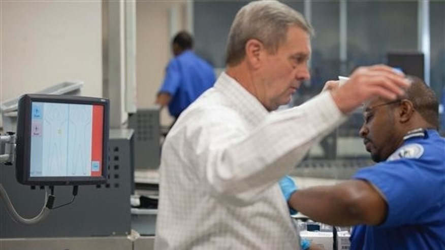 Oct. 4: A passenger is searched after going through a body scan machine at a security line at Hartsfield-Jackson International Airport in Atlanta. The Transportation Security Administration unveiled a pilot program to pre-screen a small group of select air travelers who volunteer more personal information about themselves so they can be vetted to get faster screening at airport checkpoints.
