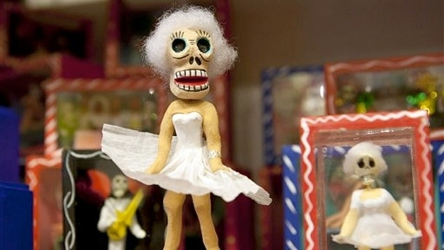 Oct. 3, 2011: A Day of the Dead skeleton figurine designed around a Marilyn Monroe theme stands on a shelf at the store Masks y Mas in Albuquerque, N.M.