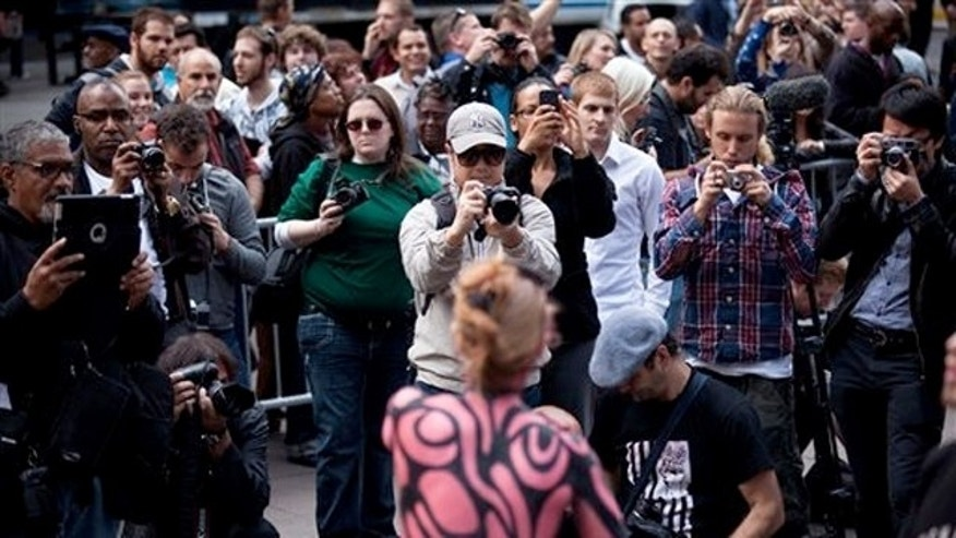 Oct. 18, 2011: Spectators swarm the Occupy Wall Street protests with their cameras in Zuccotti Park in New York.