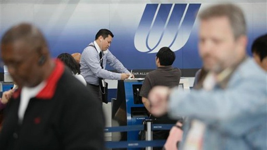 A United gate agent checking in passengers at the United Airlines terminal at Chicago's O'Hare International Airport.