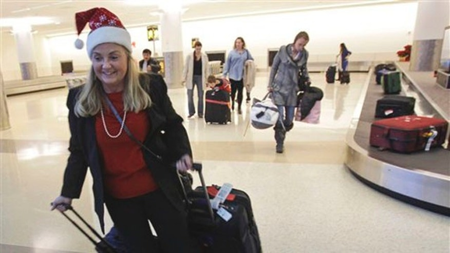 Holiday travelers collect their luggage at the San Jose International Airport in San Jose, Calif.