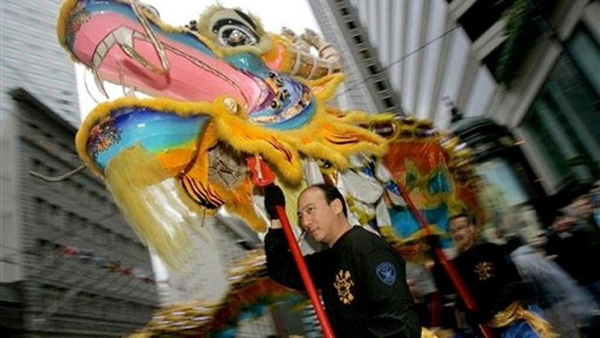 File: Neil Wu carries a dragon head as he marches with the San Francisco Police Lion Dance Team during the Chinese New Year Parade for the Year of the Rooster in San Francisco. The Year of the Dragon is approaching, that mythical, fabulous beast that is the mightiest sign in the Chinese zodiac.