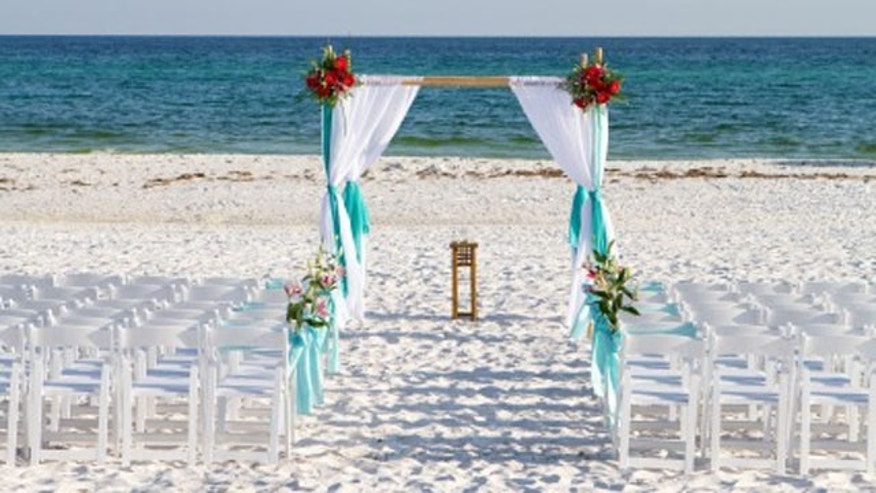 Wedding archway, chairs and flowers are arranged on the sand in preparation for a beach wedding ceremony.