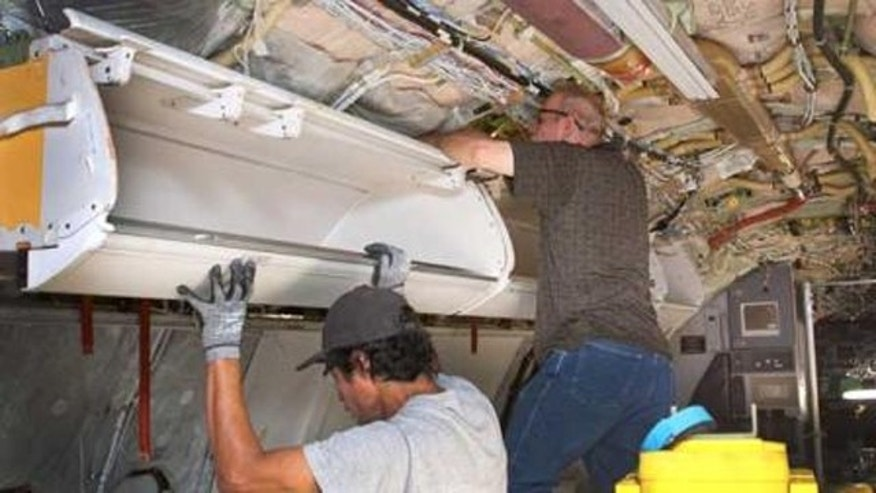 FILE: Workers installing larger bins for carry-on luggage on a Boeing 737 for American Airlines in Tulsa, Okla.