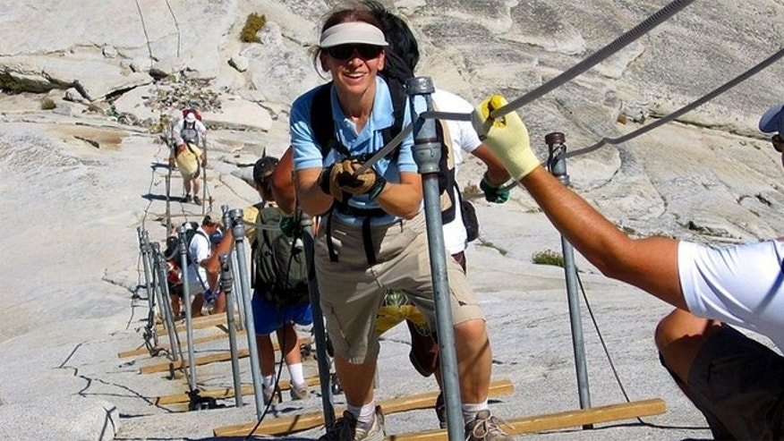 Hikers at Yosemite climb with the help of cables.
