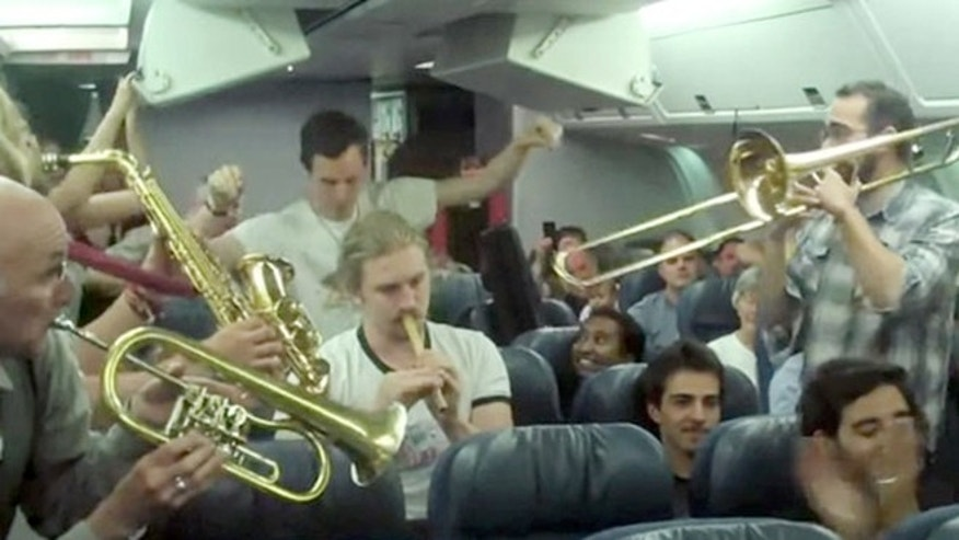 The band Lemon Bucket Orkestra playing on the delayed Air Canada flight.