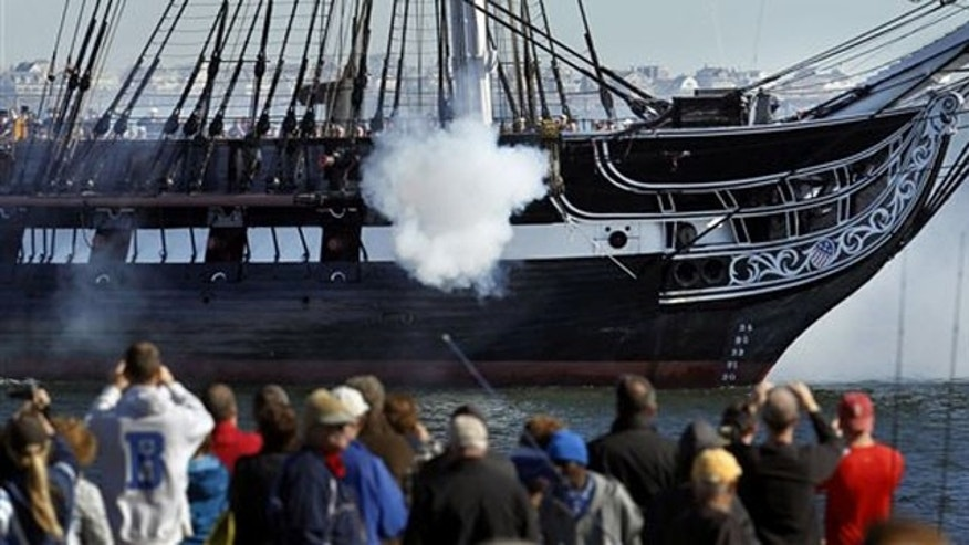The USS Constitution, which was an important vessel in the U.S. fleet during the War of 1812, fires guns in Boston Harbor.