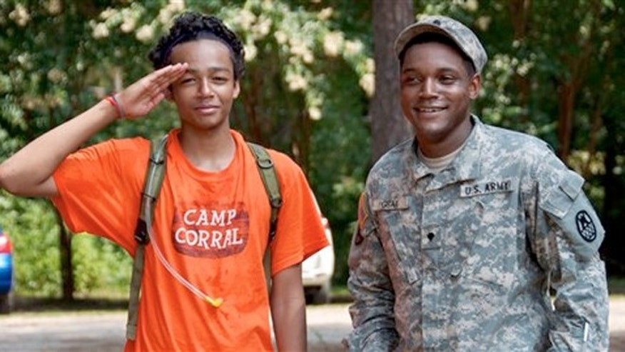 May 22, 2012: Brandon Parker of Summerville, S.C., left, enjoys a special military demonstration day with NC National Guardsman Gray at Camp Corral, a free week-long summer camp experience for the children of families with fallen, wounded or disabled veterans or service members.