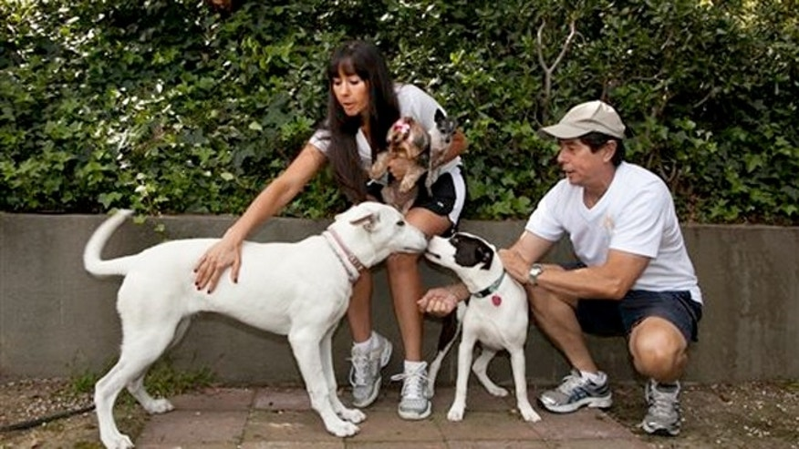May 11, 2012:  DogVacay host and home owner Tracie Sorrentini, left, holds her small dogs, Punky, left, and Puccini.