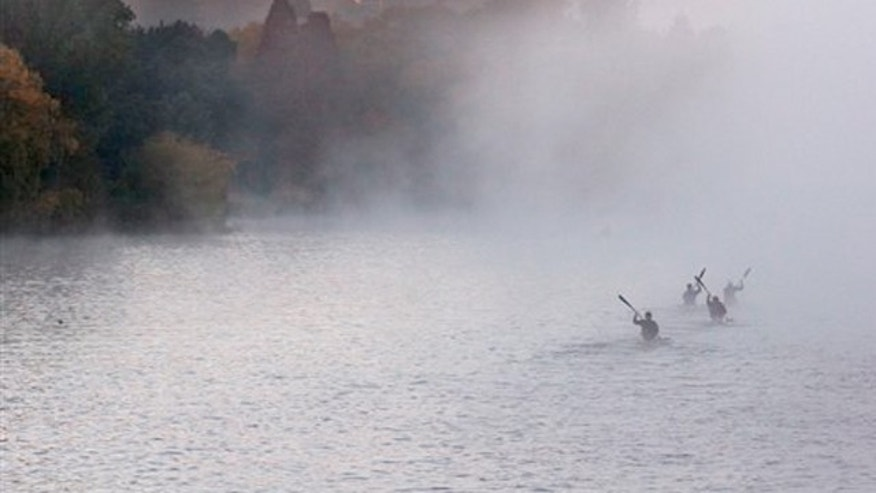 Paddlers row in the early morning autumn mist on the Emmarentia Dam in Johannesburg.