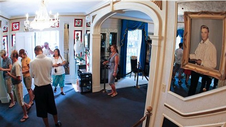 FILE -- This  Aug. 2010 photo shows tourists arriving through the front door of Graceland, Elvis Presley's home in Memphis, Tenn. Graceland opened for tours on June 7, 1982. They sold out all 3,024 tickets on the first day and didn't look back, forever changing the Memphis tourist landscape while keeping Elvis and his legend alive.(AP Photo/Mark Humphrey)