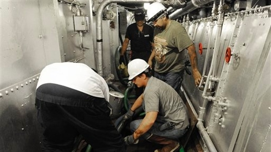 June 13, 2012: Men work to pump water from below the decks of the USS Texas. The 100-year-old battleship has been taking on as much as 1,000 gallons of seawater every minute.