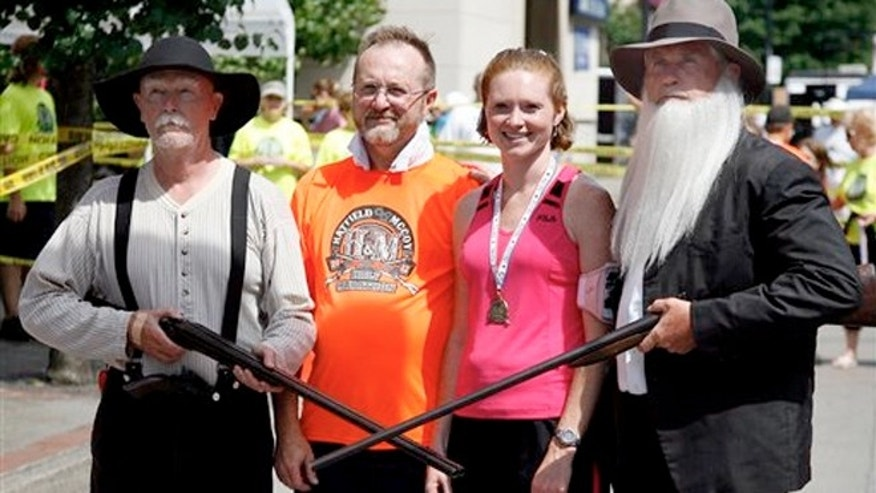 June 9, 2012: Doyle Van Meter, left, dressed as Randall McCoy and Jerry Akers, right, as Devil Anse Hatfield pose with runners after they finish the Hatfield-McCoy Marathon in Williamson, W.V.