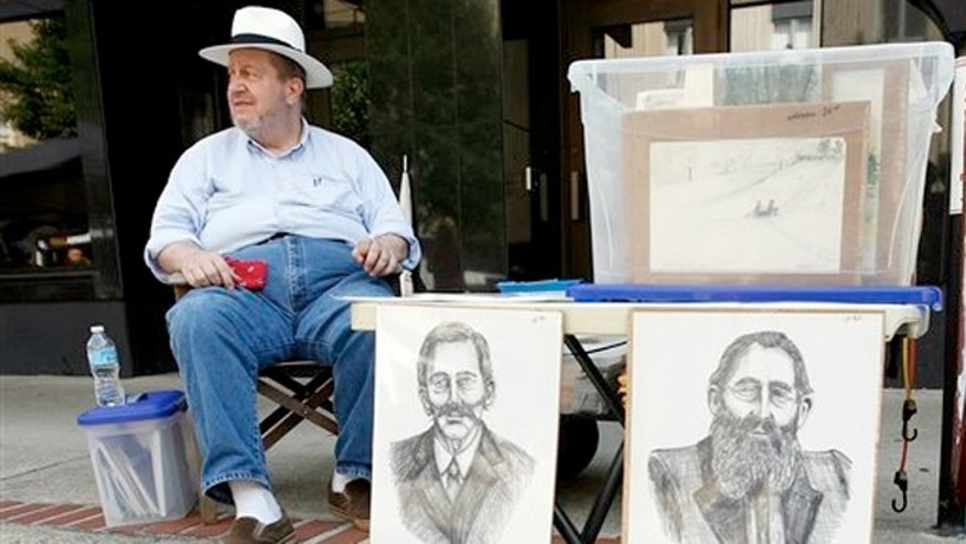 June 9, 2012: Artist J.D. Hall sells his artwork which includes prints of Randolph McCoy, left, and Devil Anse Hatfield during the Hatfield-McCoy Reunion in Williamson, W.V. A