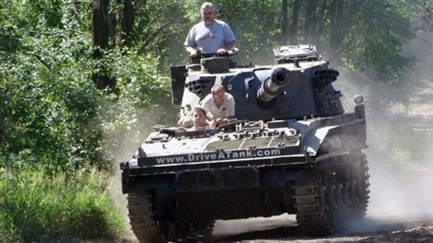 June 9, 2012: Nick Walker of Amboy, Indiana drives a tank in Kasota, Minn., while his father Brad Walker looks out from the turret.