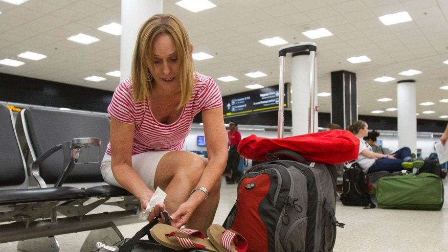 June 29, 2012: In this photo, Pat Burns, of San Diego, prepares her luggage for check-in at Miami International Airport in Miami. Burns, after an overnight stay in Miami, is traveling to the Galapagos Islands in Ecuador for the Fourth of July holiday.