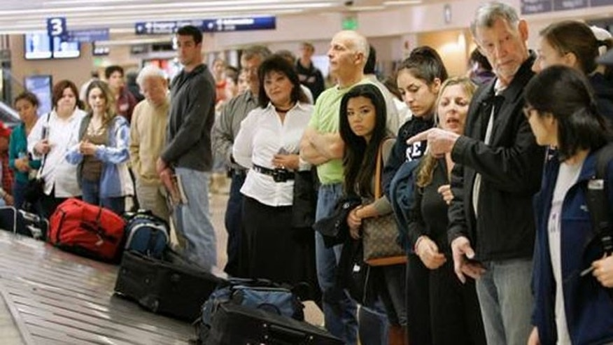 Travelers line up to get their luggage in the Southwest Airlines baggage claim at the San Jose International airport in San Jose, Calif.