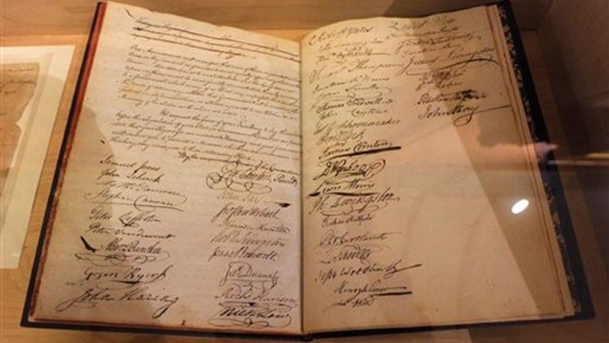 July 31, 2012: Signatures of delegates, including Alexander Hamilton and John Jay, who ratified the U.S. Constitution, fill pages of a convention journal on display at the Capitol in Albany, N.Y.