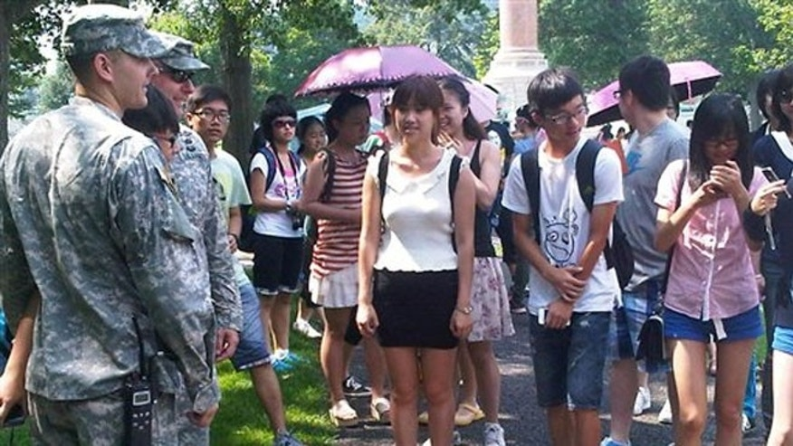 Aug. 3, 2012: A tourist poses with cadets for a photo as others wait their turn during a tour of the U.S. Military Academy at West Point, N.Y.