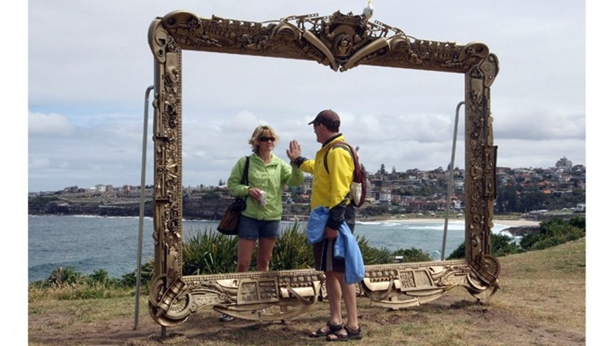 Nov. 3, 2011: A couple pretend to be a mirror image of each other in Jane Gilling's sculpture, Provenance (a gift frame) at Sculptures By The Sea.
