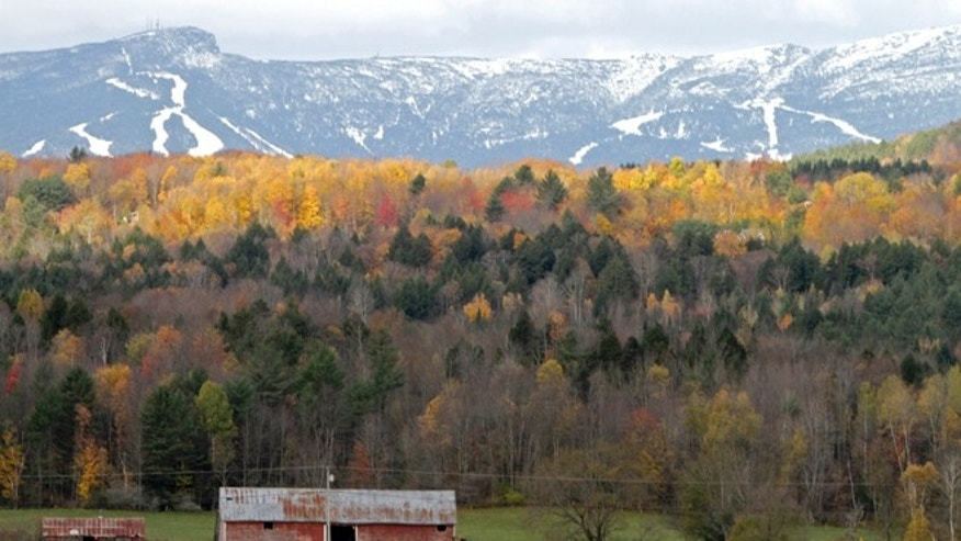 Oct. 18, 2010: Sunlight falls on remaining bright foliage as the snow capped ski trails of Stowe ski resort are seen on the side of Mt. Mansfield in Stowe , Vt.