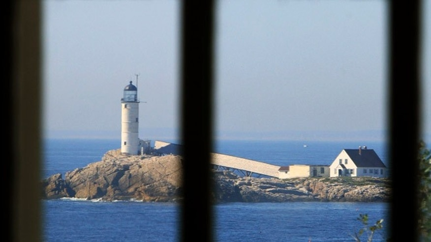The lighthouse on White Island can be seen through the church window at the Star Island Family Retreat.