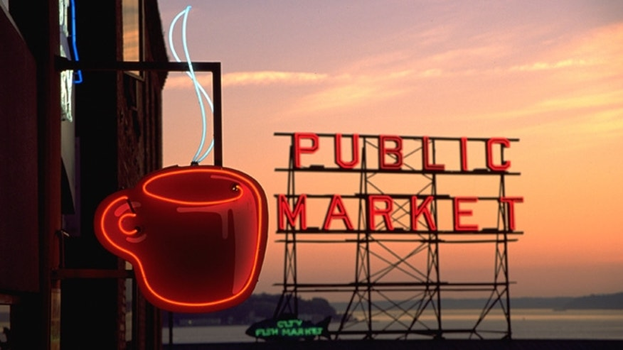 The Public Market sign hovers over the Pike Place Market, with Elliott Bay and Puget Sound in the background.
