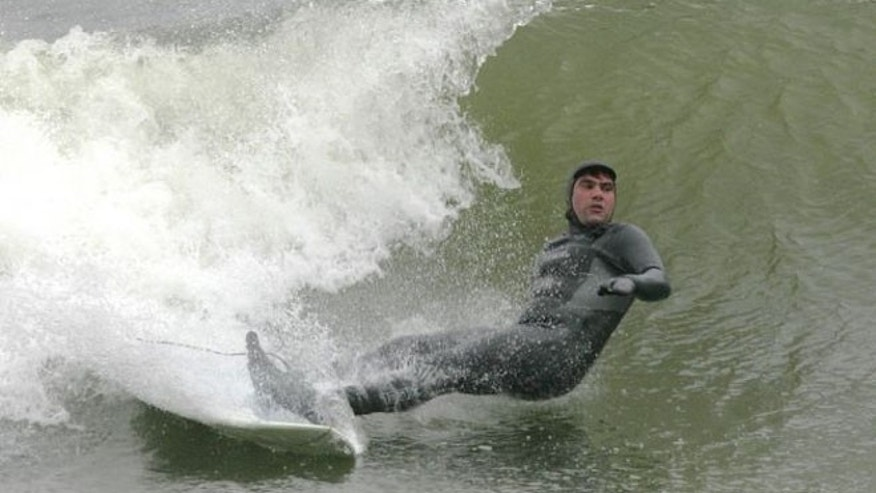 A surfer is seen off New Hampshire's coast line in Hampton, N.H.