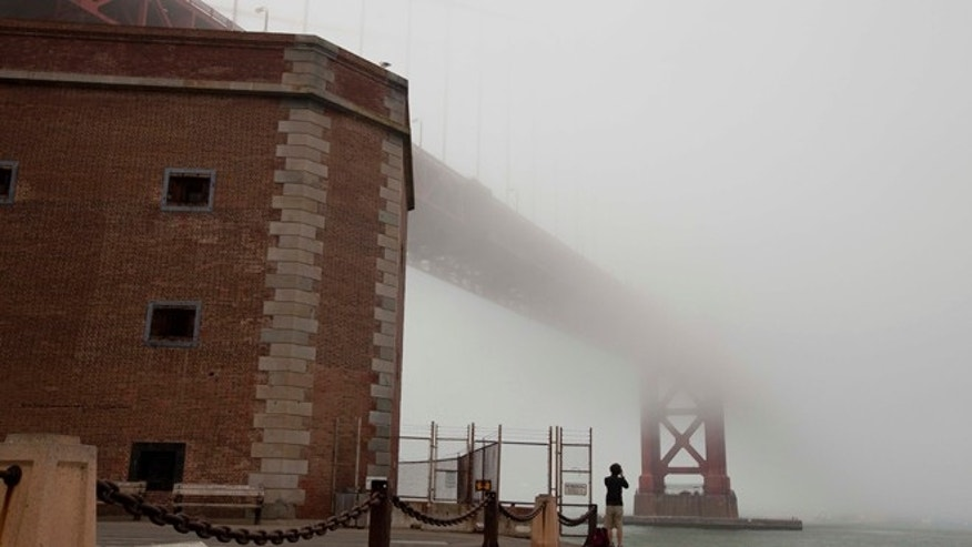 Sept. 27, 2012: A man stands beside Fort Point and looks out at the fog-covered Golden Gate Bridge in San Francisco.