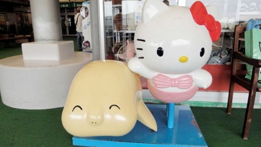 A Hello, Kitty children's ride next to a ride depicting a dugong at the Toba Aquarium in Toba, Japan.