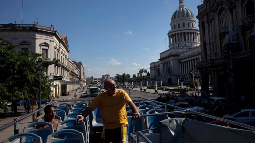 Sept 11, 2012: A tourist stands inside an open-air tourist bus in Havana, Cuba.