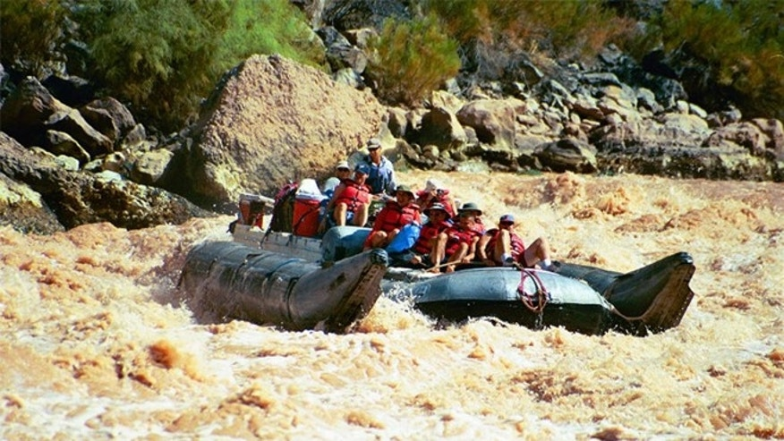 Visitors riding a pontoon raft through rapids in Grand Canyon National Park, Ariz.