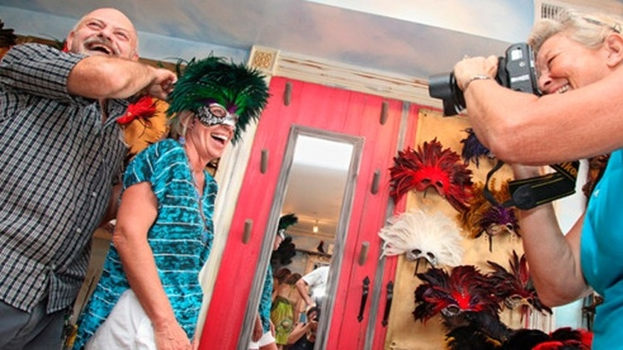 John McBride, owner of the Maskerville mask store in Key West, fitting Marty Lambeth with one of his creations.