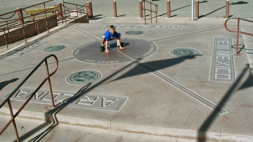 This August 2005 file photo shows a boy touching four border states, New Mexico, Arizona, Utah and Colorado at Four Corners National Monument.