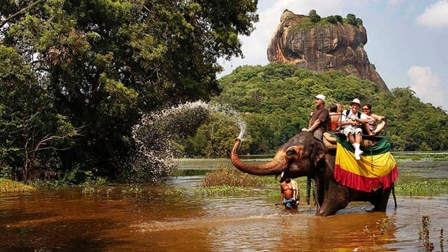Dec. 2, 2011: A tame elephant sprays water at foreign tourists during a safari ride in Sigiriya, about 100 kilometers (62 miles), north east of Colombo, Sri Lanka.