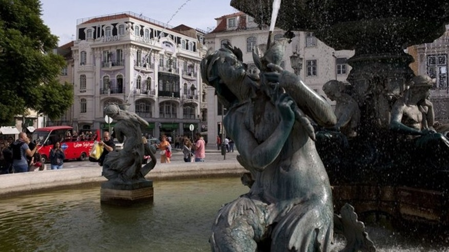 Sept. 28, 2012: Tourists take pictures by a fountain in Lisbon's central Rossio square.