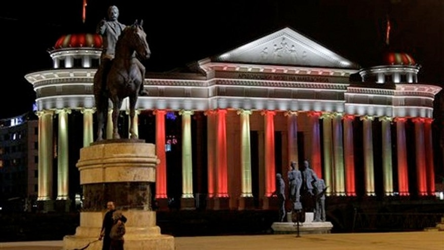 "Oct. 23, 2012: People walk by the statue of well-known revolutionary figure Goce Delcev, left and ""Boatmen of Thessaloníki"" monument, right, in front of the newly-built Museum of Archaeology in downtown Skopje, Macedonia."