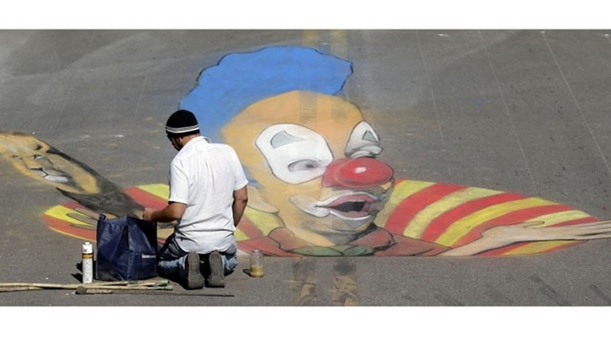 Oct. 31, 2012: Truman Adams, of Sarasota, works on his 3D pavement project during the Sarasota Chalk Festival.