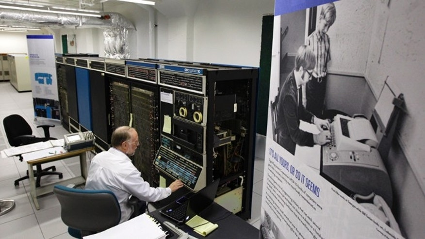 Oct. 30, 2012: Bruce Sherry, a contract engineer at the Living Computer Museum in Seattle, manually programs a DEC PDP-10 computer from the early 1970s next to a photograph of Microsoft co-founders Paul Allen, seated, and Bill Gates, standing at Allen's left, working on a teletype machine.