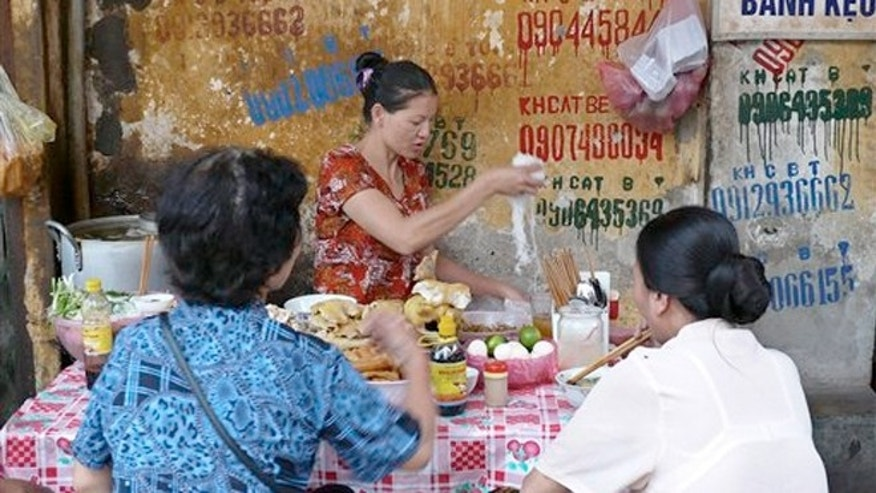 April 14, 2008: A woman cooking noodle for her customers at a stall in a street in Old Quarter district in Hanoi, Vietnam. The 36 ancient streets that make up Hanoi's Old Quarter are a maze of madness filled with treasures.
