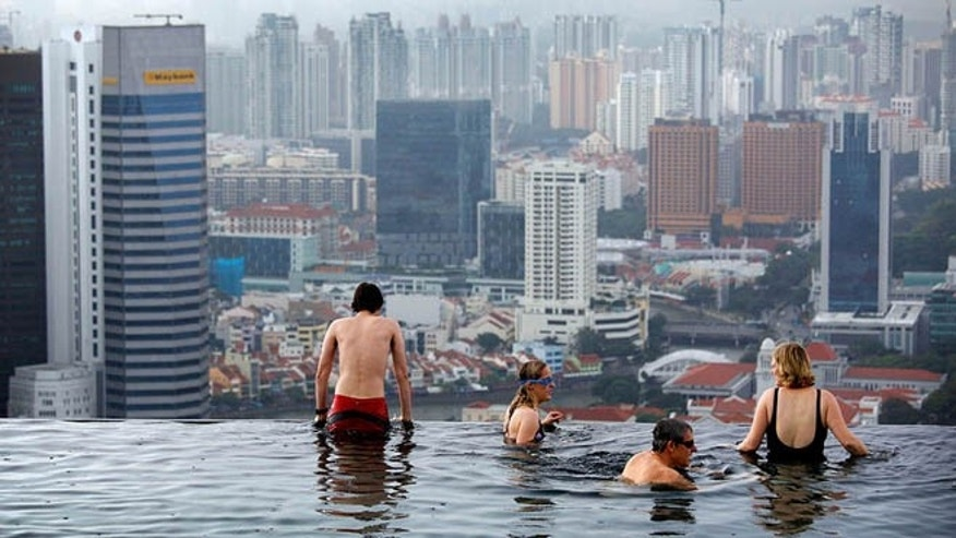Jan. 3, 2011: Tourists relax in an infinity pool on the roof of the Marina Bay Sands Hotel tower in Singapore.