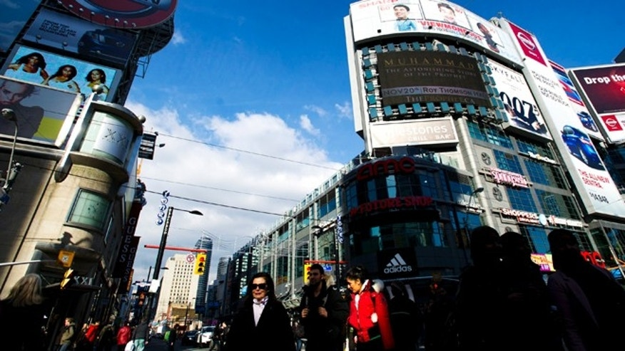 Nov. 14, 2012: People cross the street at Yonge and Dundas in the heart of downtown Toronto.