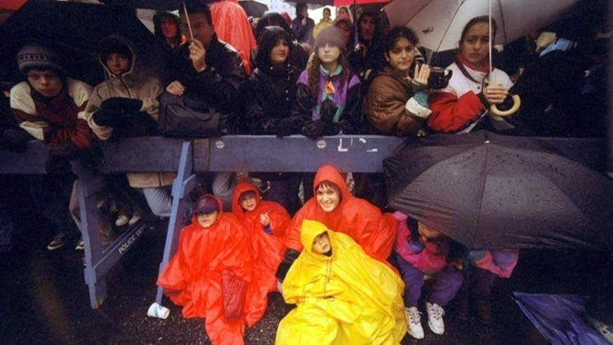 Spectators, dressed in rain gear, line the street during the 72nd annual Macys Thanksgiving Day Parade.