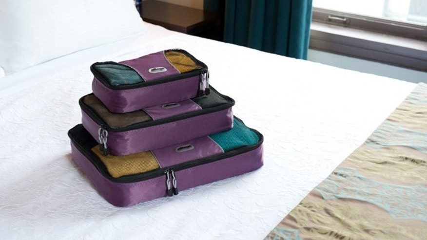 This undated image provided by eBags.com shows a set of the company's packing cubes on a bed in a hotel room.