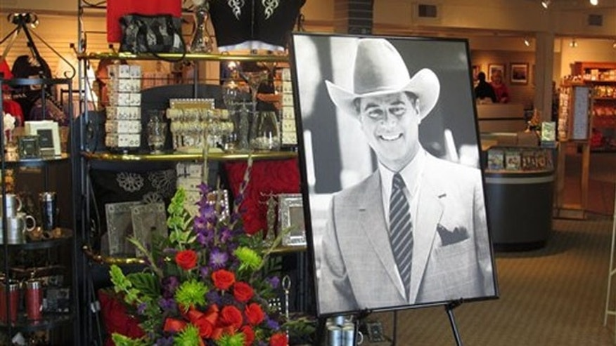 Nov. 24, 2012: A large portrait of Larry Hagman can be seen by a bouquet of flowers at the entrance of the gift shop at Southfork Ranch on Saturday.
