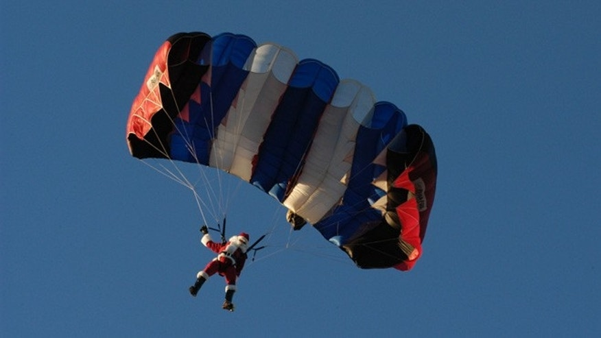 Santa parachutes in to the Festival of Lights at Moody Gardens.